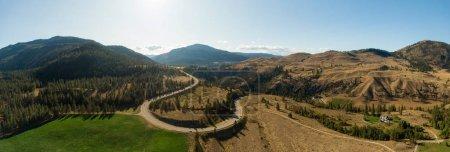 Photo pour Vue aérienne d'une route panoramique dans le paysage sec des montagnes canadiennes par une journée d'été ensoleillée. Prise à Okanagan, près de Penticton, Colombie-Britannique, Canada . - image libre de droit