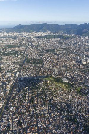 Aerial view from airplane window while flying over Complexo do Alemao Favela in north Rio de Janeiro, Brazil