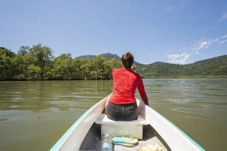Young woman with red shirt ocean kayaking in the rainforest near mangrove vegetation, Saco do Mamangua, Paraty, Costa Verde region in south Rio de Janeiro, Brazil