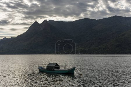 Beautiful tropical landscape with green rainforest and small local boat in the ocean in Saco do Mamangua, Paraty, Costa Verde region in south Rio de Janeiro, Brazil