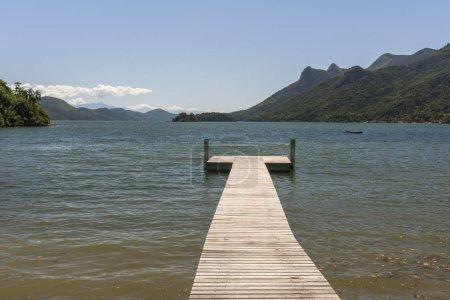 Empty pier on deserted beach with beautiful atlantic rainforest and blue ocean landscape, Paraty, Costa Verde region in south Rio de Janeiro, Brazil