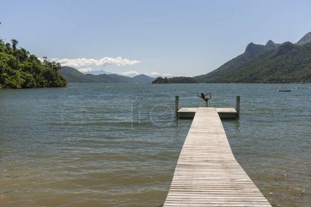 Woman practicing yoga on wooden pier with beautiful tropical rainforest and ocean landscape, Saco do Mamangua, Paraty, Costa Verde region in south Rio de Janeiro, Brazil