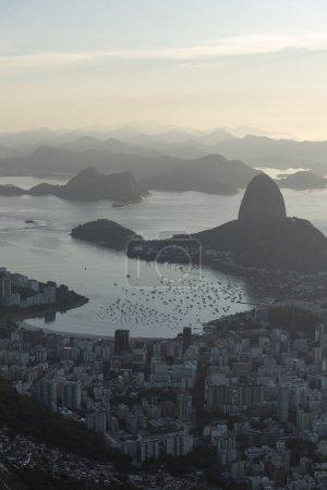 Photo pour Beau paysage en vue de la région de la baie de pain de sucre, la ville et les montagnes à partir de Christ la Statue du Rédempteur (Cristo Redentor) au sommet de la montagne du Corcovado (Morro do Corcovado) pendant le lever du soleil de Rio de Janeiro, Brésil - image libre de droit
