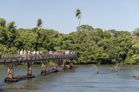 Tourists enjoying beautiful landscape of big waterfalls on green