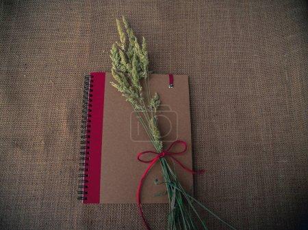 Photo pour Style vintage. Bureau organisé avec ordinateur portable fermé, herbe sèche et fond de toile de jute - image libre de droit