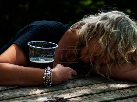Photo for A drunk woman with a glass of beer in her hand, unconscious, leaning on a table - Royalty Free Image