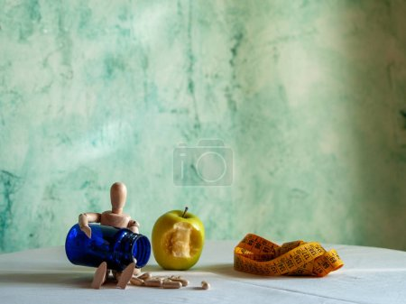 Photo pour Une figurine avec une pomme mordue, un ruban à mesurer et un récipient bleu avec des pillules de fibre végétale sur une table - image libre de droit