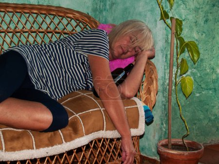 Photo for A drunk senior woman with a wine bottle in her hand, unconscious, lying down in a sofa - Royalty Free Image