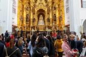El Rocio, Huelva, Spain - April 30, 2017: People praying in front of altarpiece at the high altar in El Rocio hermitage, Huelva, Spain