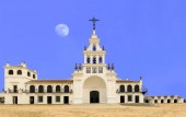 El Rocio hermitage with full moon in a clear blue sky at small village with the same name in Almonte, Huelva, Andalusia, Spain