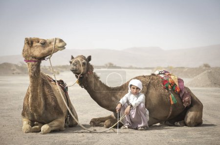 AL Safen, Oman, April 27, 2018: Bedouin boy standing with camels in Omani countryside.
