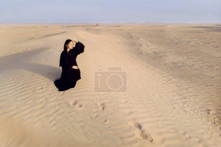 woman in a traditional emirati dress called abaya in a desert near Dubai