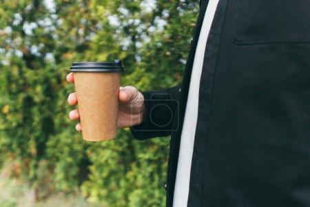 Photo pour Homme attrayant boire et profiter du café d'une tasse à l'extérieur du café dans la rue - image libre de droit