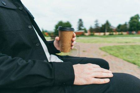 Photo pour Un homme assis sur un banc tient un café tout en marchant dans le parc - image libre de droit