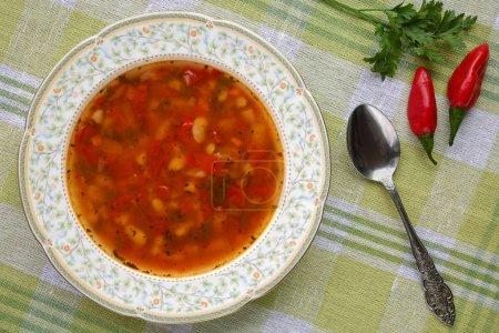 Foto de Sopa de frijoles búlgaro tradicional deliciosa casera (bob chorba) con pimiento, tomate, cebolla y especias, servido con pimientas - Imagen libre de derechos