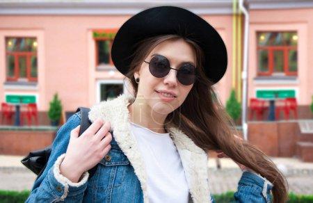 Photo pour Une belle jeune fille européenne, souriant à l'arrière-plan de la ville - image libre de droit