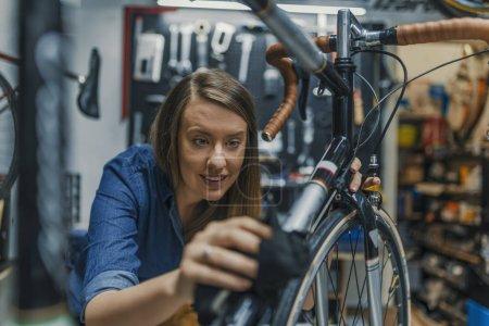 Photo pour Femmes essuie vélo. Femme professionnelle qui travaille dur en polissant le matériel de vélo dans l'atelier. Mécanicien réparer vélo dans son atelier - image libre de droit