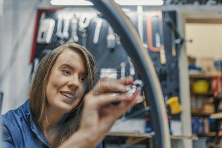 Focused On Tightening Bicycle Tire. Watchful technician mending the bicycle in the repair shop. Girl repair bicycle wheel. Woman bike mechanic working on bicycle