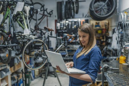 Young female mechanic with laptop. Business woman at a factory. Woman mechanic working on a laptop. Female Bicycle Mechanic.