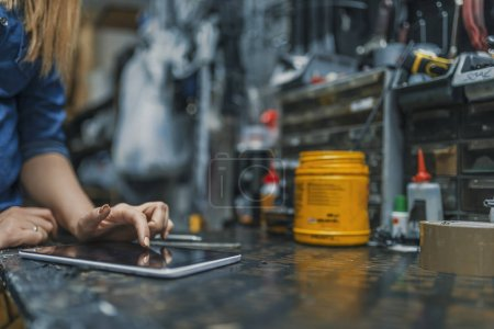 Female mechanic at work. Using a tablet while fixing a bicycle. Female bicycle repair technician using digital tablet in bicycle shop. Mechanic woman checking something on a tablet-pc and checklist