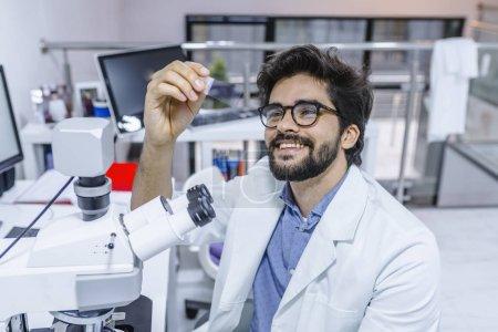 Photo pour Scientifique des recherches en laboratoire. Scientifique examine des échantillons de biopsie. Chercheur de mâle satisfait souriant joyeusement tout en siégeant à un microscope et en examinant un échantillon dans ses mains - image libre de droit