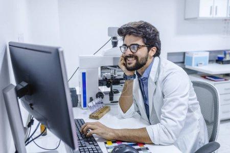 Photo pour Sympathique médecin de sexe masculin est assis à la table et travaillant au bureau de l'hôpital. Prêt à examiner et à aider les patients. Haut niveau et qualité médicale concept de service - image libre de droit
