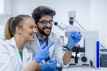 Foto de Dos biotecnólogos comunicarse mientras se trabaja en investigación en un laboratorio. Colegas que trabajan en la investigación científica en el laboratorio. concepto de ciencia, química, tecnología, biología y personas - Imagen libre de derechos