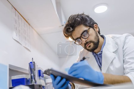 Male doctor consults with his patient and writes notes on the clipboard. Doctor with pen writing on prescription blank. healthcare, hospital and medical concept