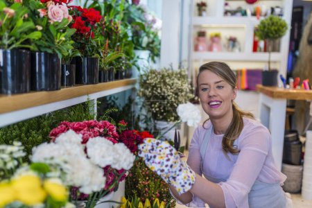 Smiling woman florist small business flower shop owner. Small business concept with florist woman ownership on modern flower shop. Flowers delivery, creating order.