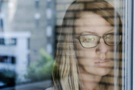 Photo pour Seule fille réfléchie debout à la fenêtre - image libre de droit
