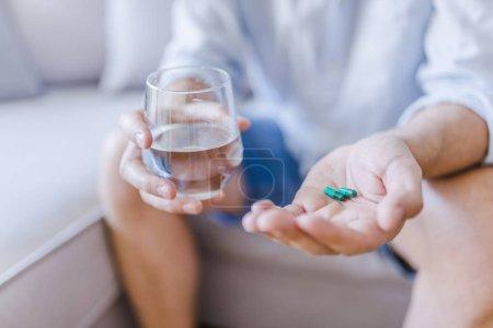 Photo pour Jeune homme avec la pilule et le verre d'eau à la maison, agrandi. Jeune homme qui prennent des médicaments, sentez pas. Concept de soins de santé. L'homme déprimé détient antidépresseur meds - image libre de droit
