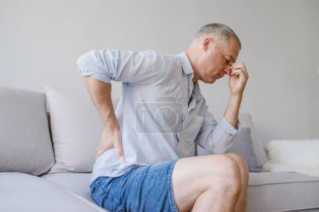 Photo for Man suffering from back pain at home. Unhappy mature man suffering from pain in back or reins at home. People, healthcare and problem concept - Royalty Free Image