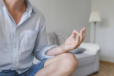 Photo for Relaxed handsome young man sitting and meditating. Business Concept. Business man relaxing in living room in the lotus position. Close up. Young businessman sitting with legs crossed relaxing - Royalty Free Image