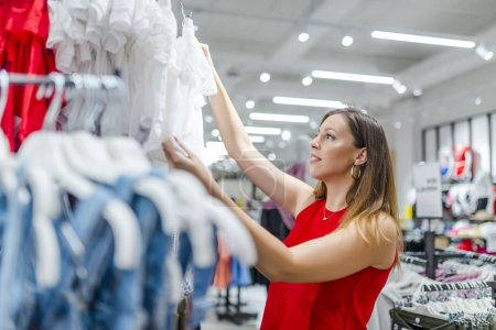 Attractive woman in boutique choosing clothes. Shopping concept - woman choosing dress during shopping at garments apparel clothing shop. Woman shopper customer choosing shirt and other clothes in a fashion store