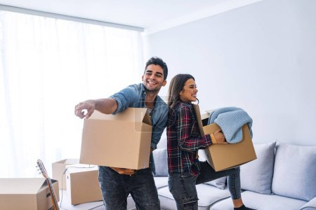 Photo for Young couple moving into new home with cardboard boxes - Royalty Free Image