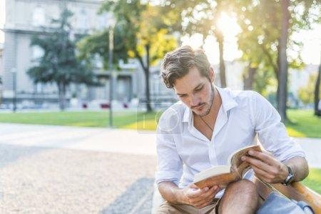 Photo pour Jeune homme lisant un livre dans un parc municipal - image libre de droit