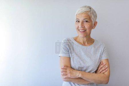 Photo pour Femme âgée souriante appliquant une lotion anti-âge pour enlever les cernes sous les yeux. Heureuse femme mûre utilisant la crème cosmétique pour cacher les rides sous les yeux. Dame utilisant hydratant jour . - image libre de droit