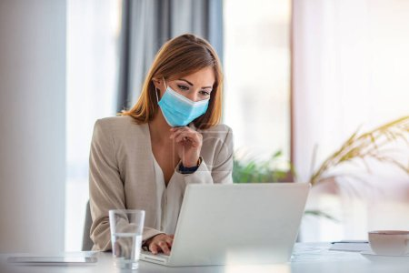 Photo for Female employee wearing medical face mask while working in the business office during covid-19 pandemic. Businesswoman wearing face mask while analzying reports in the office. - Royalty Free Image