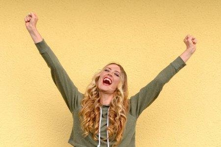 Photo pour Heureux jeune femme joyeuse acclamations élever ses poings en l'air alors qu'elle célèbre un succès ou la bonne nouvelle sur un fond jaune studio - image libre de droit