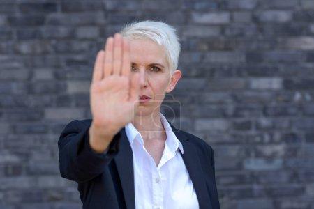 Photo pour Femme faisant un geste stop ou arrêt avec sa main dans un front Découvre le focus sur le visage - image libre de droit