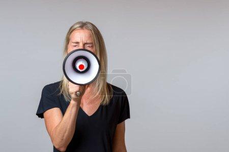 Photo pour Femme en colère criant dans un mégaphone portable dans un concept d'activisme, grève, manifestation, protestation ou parler en public sur gris avec espace de copie - image libre de droit