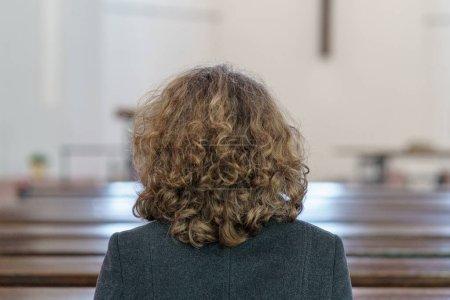 Photo pour Vue de dos d'une femme religieuse d'âge mûr de dévot priant dans une église agenouillée seule dans un banc - image libre de droit