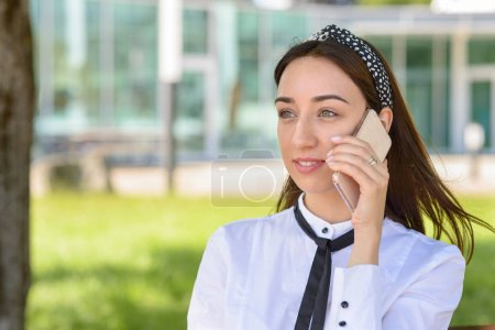 Photo for Young woman listening to a call on her mobile phone with a serious thoughtful expression outdoors in an urban park - Royalty Free Image