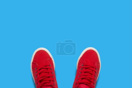 Red sneakers on a blue background. Minimalism style. Flat lay, top view.