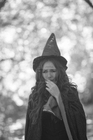 eine Hexe süße Hexe. ein attraktives Mädchen mit Mütze flüstert eine Verschwörung. Zauber