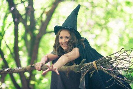 Hexe an Halloween. Porträt eines süßen Mädchens. schelmische Zauberin. attraktives und sexy Mädchen mit Besen und Hexenhaube