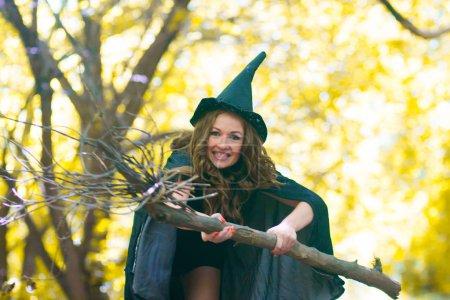 eine Hexe auf einem Besen inmitten des Waldes. Porträt eines süßen Mädchens. schelmische Zauberin. sexy Mädchen mit Besen und Hexenhaube im Regenmantel