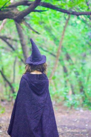 Hexe mit Kapuze und Mantel im Wald. Konzept von halloween