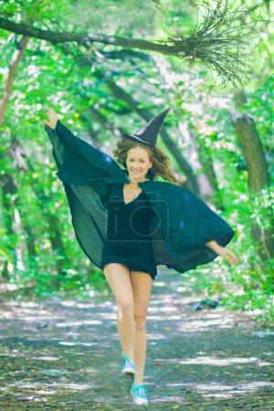 eine Fee mit Kapuze und Mantel inmitten des Waldes. eine fröhliche Hexe. springt. Konzept von halloween