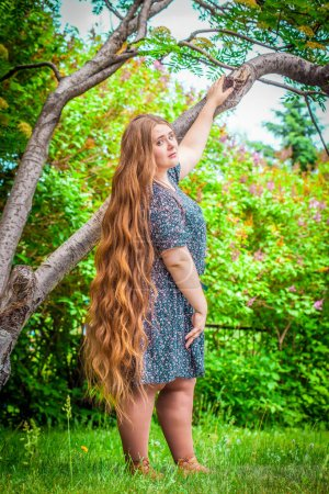 Photo for Beautiful plump girl with long hair. Plus size model posing against nature background. - Royalty Free Image